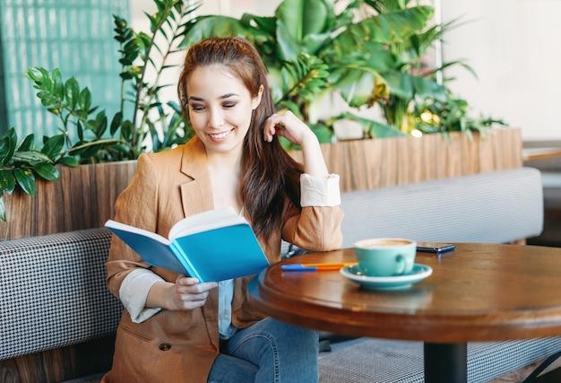 Jonge brunette aziatische studente leesboek met koffie op tafel in het café