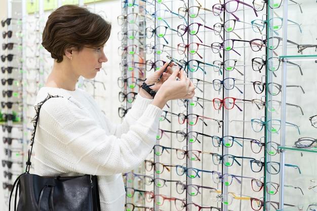Jonge brunette bril bedrijf in haar handen in een professionele optica winkel, boetiek verkopen optica voor visie.