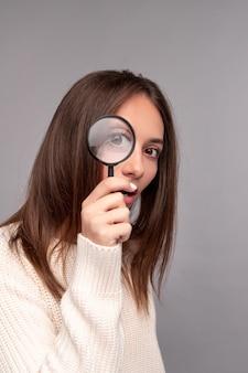 Jonge brunette die in gebreide trui met belangstelling door vergrootglas kijkt