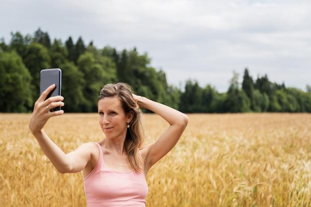 Jonge brunette die selfies met haar mobiele telefoon maakt die zich buiten in mooi gouden gebied bevindt.