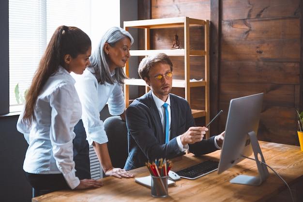 Jonge brunette en grijze haren luisteren naar hun mannelijke collega die naar computermonitor wijst