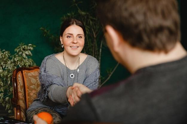 Jonge brunette europese vrouw psycholoog met een glimlach schudt handen met een patiënt die tegenover haar zit