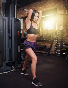 Jonge brunette fit vrouw uitvoeren oefening voor triceps met hometrainer cable crossover in sportschool. trainingsproces