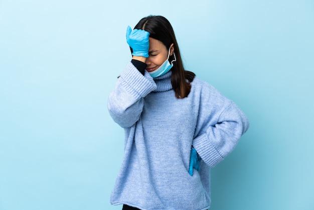 Jonge brunette gemengd ras vrouw beschermen met een masker en handschoenen over blauwe muur met hoofdpijn