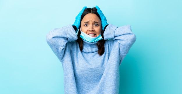 Jonge brunette gemengd ras vrouw beschermen tegen het coronavirus met een masker en handschoenen over geïsoleerde blauwe muur nerveus gebaar doen