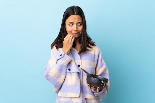 Jonge brunette gemengd ras vrouw met een kom vol met noedels over blauwe muur nerveus en bang handen naar mond brengen