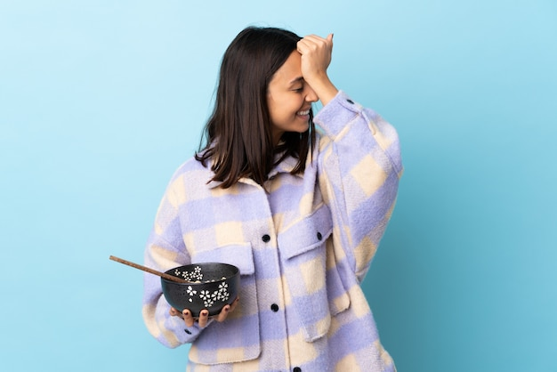 Jonge brunette gemengd ras vrouw met een kom vol noedels over blauwe muur heeft iets gerealiseerd en van plan de oplossing