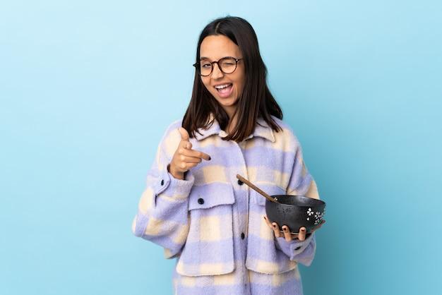 Jonge brunette gemengd ras vrouw met een kom vol noedels over geïsoleerde blauw wijst naar de voorkant en glimlachen