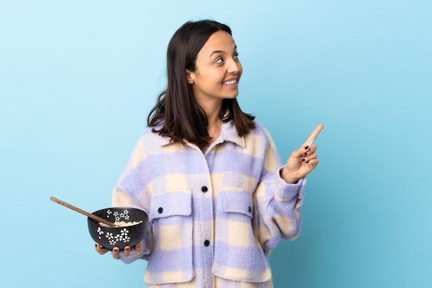 Jonge brunette gemengd ras vrouw met een kom vol noedels over geïsoleerde blauwe achtergrond met een geweldig idee.