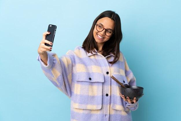 Jonge brunette gemengd ras vrouw met een kom vol noedels over geïsoleerde blauwe muur maken van een selfie