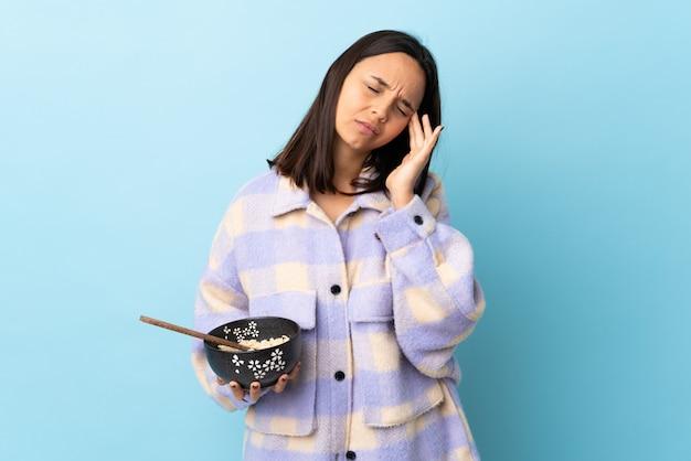 Jonge brunette gemengd ras vrouw met een kom vol noedels over geïsoleerde blauwe muur met hoofdpijn