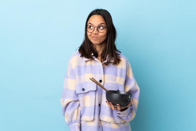 Jonge brunette gemengd ras vrouw met een kom vol noedels over geïsoleerde blauwe muur twijfels tijdens het kijken.