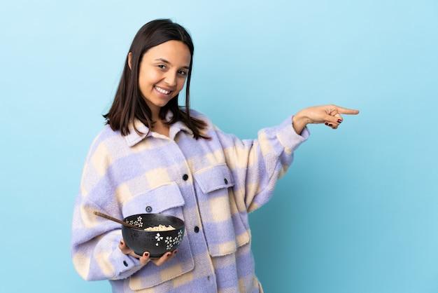 Jonge brunette gemengd ras vrouw met een kom vol noedels over geïsoleerde blauwe muur wijzende vinger naar de zijkant en het presenteren van een product