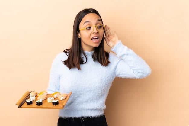 Jonge brunette gemengd ras vrouw met sushi over geïsoleerde achtergrond luisteren naar iets door hand op het oor te leggen