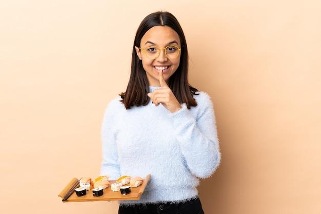 Jonge brunette gemengd ras vrouw met sushi over geïsoleerde achtergrond met een teken van stilte gebaar vinger in de mond steken
