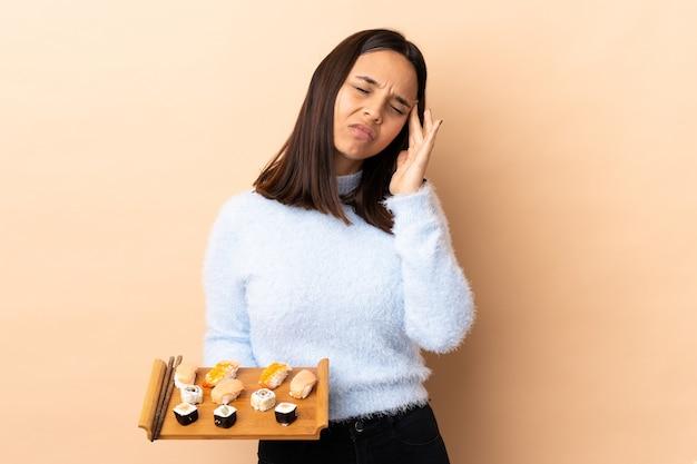 Jonge brunette gemengd ras vrouw met sushi over geïsoleerde achtergrond met hoofdpijn