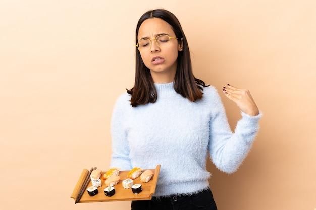 Jonge brunette gemengd ras vrouw met sushi over geïsoleerde achtergrond met vermoeide en zieke uitdrukking