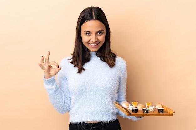 Jonge brunette gemengd ras vrouw met sushi over geïsoleerde achtergrond ok teken met vingers tonen