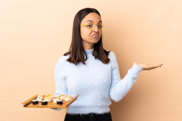 Jonge brunette gemengd ras vrouw met sushi over geïsoleerde achtergrond twijfels