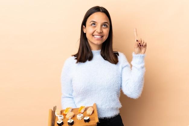 Jonge brunette gemengd ras vrouw met sushi over geïsoleerde een geweldig idee naar voren