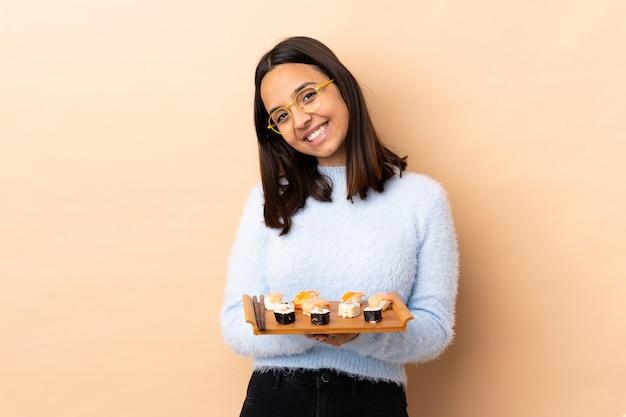Jonge brunette gemengd ras vrouw met sushi over geïsoleerde houd palm samen. persoon vraagt iets
