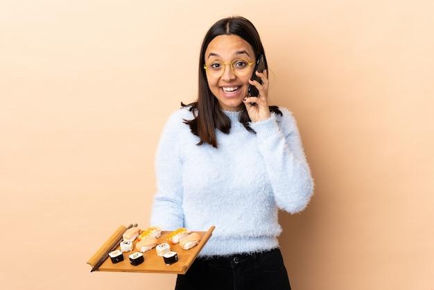 Jonge brunette gemengd ras vrouw met sushi over geïsoleerde houden een gesprek met de mobiele telefoon met iemand