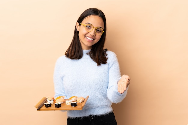 Jonge brunette gemengd ras vrouw met sushi over geïsoleerde muur handen schudden voor het sluiten van een goede deal