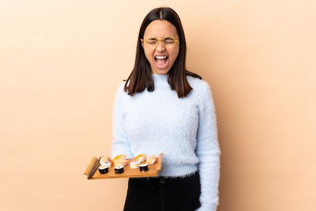Jonge brunette gemengd ras vrouw met sushi over geïsoleerde muur schreeuwen naar voren met wijd open mond