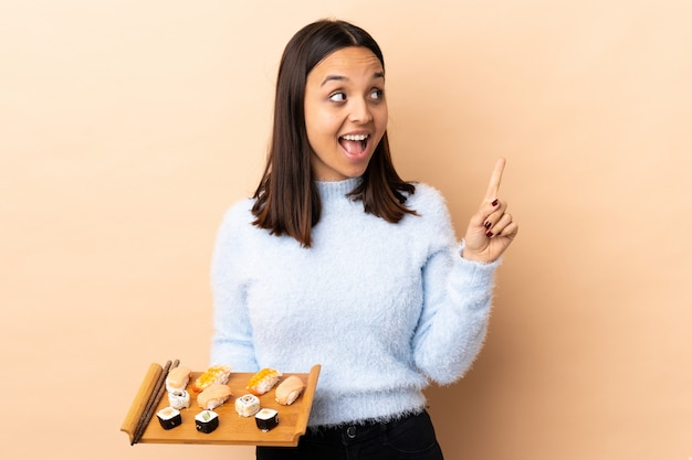 Jonge brunette gemengd ras vrouw met sushi over geïsoleerde van plan om de oplossing te realiseren