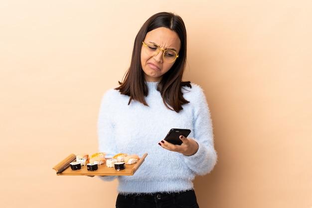 Jonge brunette gemengd ras vrouw met sushi over muur denken en het verzenden van een bericht
