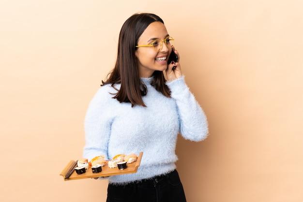 Jonge brunette gemengd ras vrouw met sushi over muur houden een gesprek met de mobiele telefoon