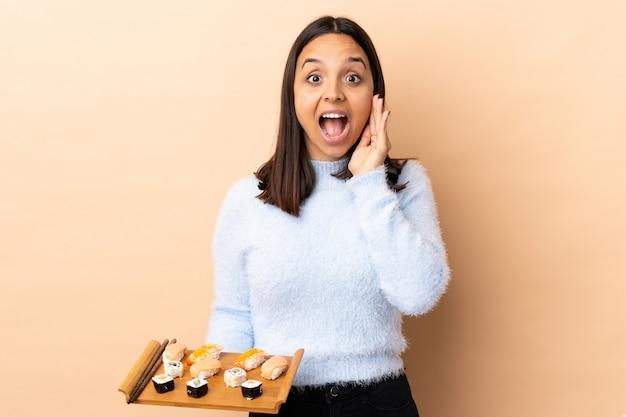 Jonge brunette gemengd ras vrouw met sushi over muur met verrassing en geschokte gelaatsuitdrukking