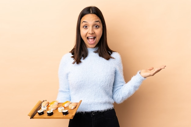 Jonge brunette gemengd ras vrouw met sushi