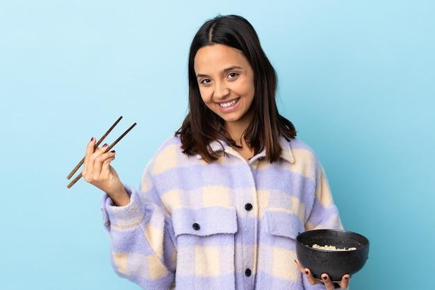 Jonge brunette gemengd ras vrouw over blauwe muur met een kom noedels met stokjes