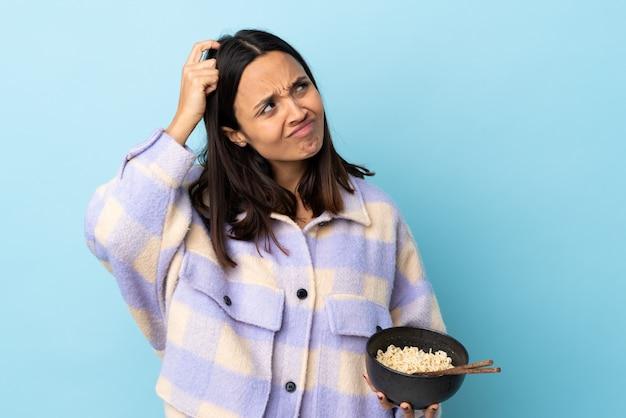 Jonge brunette gemengd ras vrouw over blauwe muur twijfels en met verwarde gezichtsuitdrukking terwijl een kom noedels met stokjes