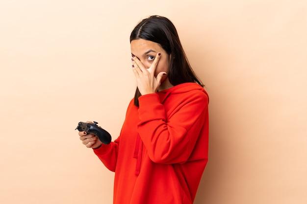 Jonge brunette gemengd ras vrouw spelen met een video game controller