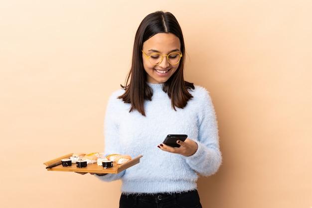 Jonge brunette gemengde de holdingssushi van de rasvrouw over geïsoleerde achtergrond die een bericht met mobiel verzenden