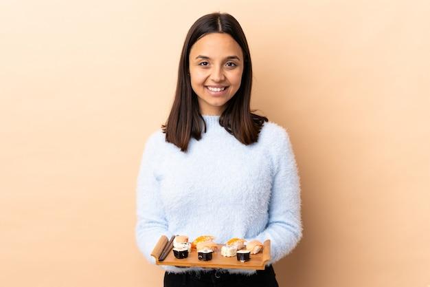 Jonge brunette gemengde ras vrouw met sushi over geïsoleerde muur lachen
