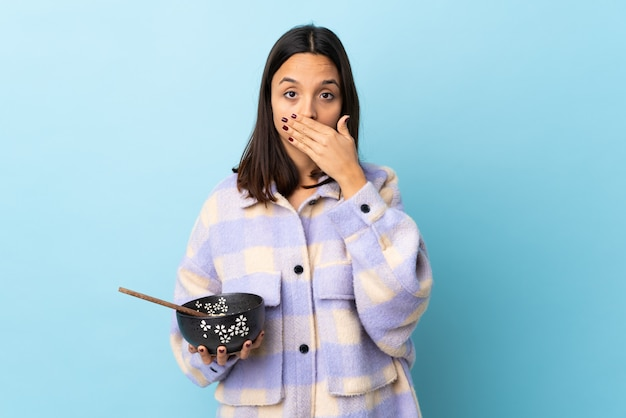 Jonge brunette gemengde rasvrouw die een komhoogtepunt van noedels over geïsoleerde blauwe achtergrond houdt die mond behandelt met handen