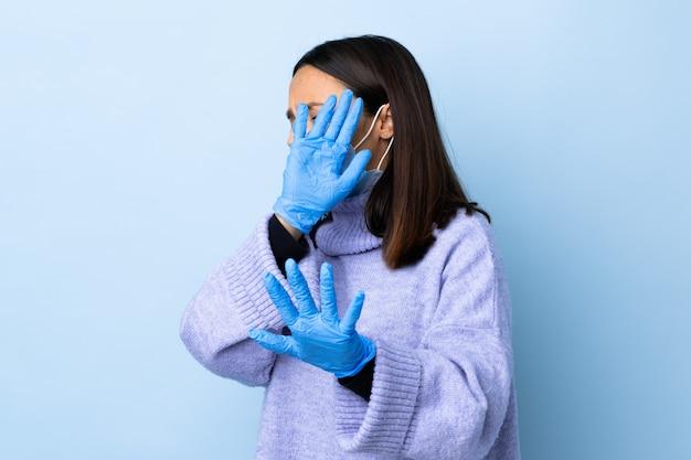 Jonge brunette gemengde rasvrouw die met een masker en handschoenen over blauwe muur zenuwachtige uitrekkende handen aan de voorzijde beschermt