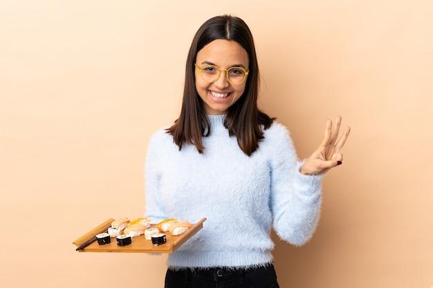 Jonge brunette gemengde rasvrouw die sushi over geïsoleerde muur gelukkig houdt en drie met vingers telt