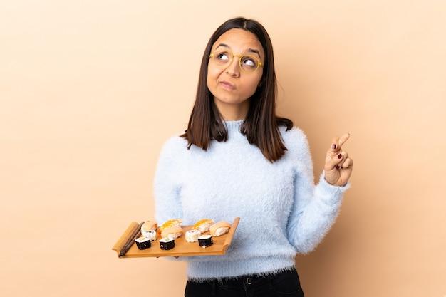 Jonge brunette gemengde rasvrouw die sushi over geïsoleerde muur met vingers kruisen en het beste wensen