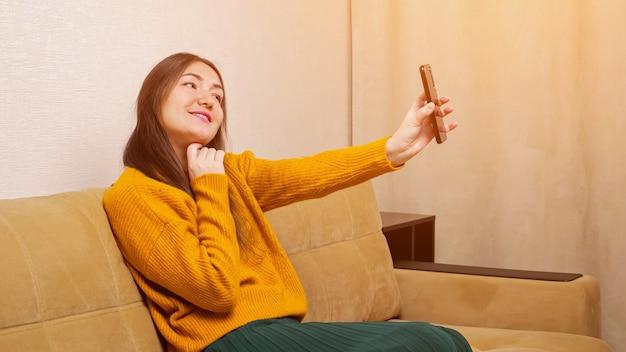 Jonge brunette houdt smartphone vast en poseert voor de camera