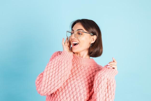 Jonge brunette in roze trui geïsoleerd op blauwe muur