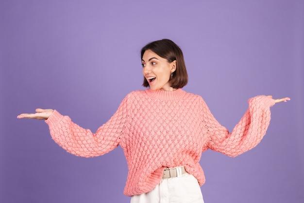 Jonge brunette in roze trui geïsoleerd op paarse muur