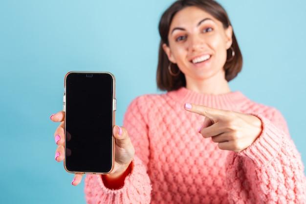 Jonge brunette in warme roze trui geïsoleerd op blauwe muur