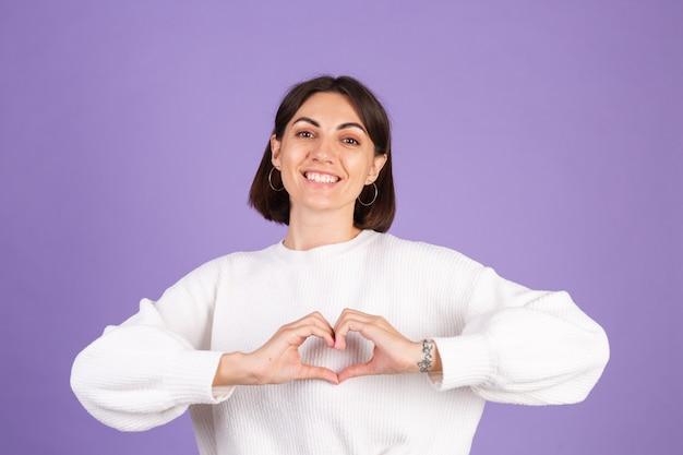 Jonge brunette in witte casual trui geïsoleerd op paarse muur