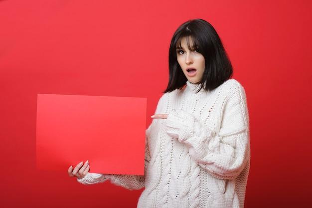 Jonge brunette in witte trui met lege rode poster wijzend met verbazing op rood