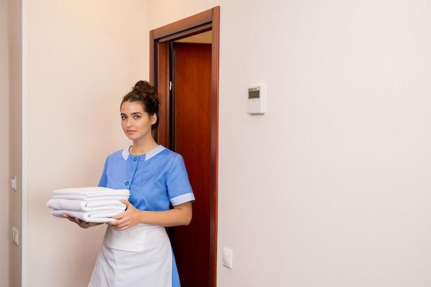 Jonge brunette kamermeisje in uniform met stapel witte schone handdoeken tijdens het verlaten van een van de hotelkamers