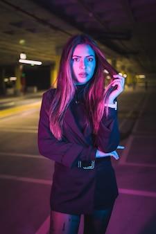 Jonge brunette kaukasisch meisje 's nachts in een ondergrondse parkeerplaats, verlicht met neonlichten
